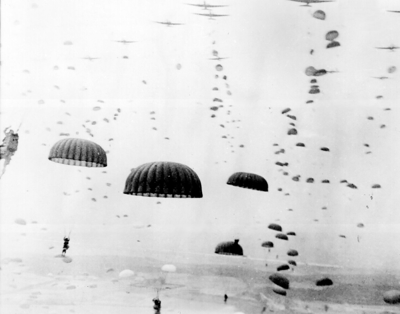 Parachutes open overhead as waves of paratroops land in Holland during operations by the 1st Allied Airborne Army. September 1944