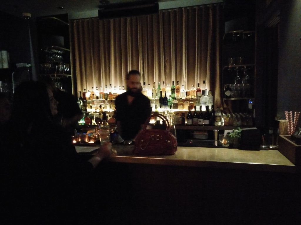 Interior (night) - FADE IN: A very mysterious red Lynchian handbag on the counter in front of a blurry bartender. (photo: Patrick von Sychowski - Celluloid Junkie)
