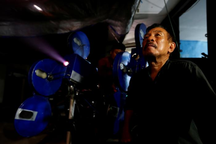 A villager sits next to a 35mm projector. (photo: Reuters / Beawiharta)