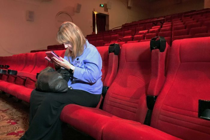 Sarah Savage checks out the app on her first visit to a cinema. (photo: ABC News / Nathan Stitt)