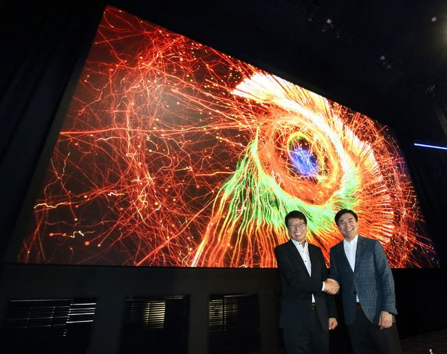 Samsung's Kim and Lotte's Chun shake hands in front of the Cinema LED 'Super S' screen. (photo: Korea Daily)