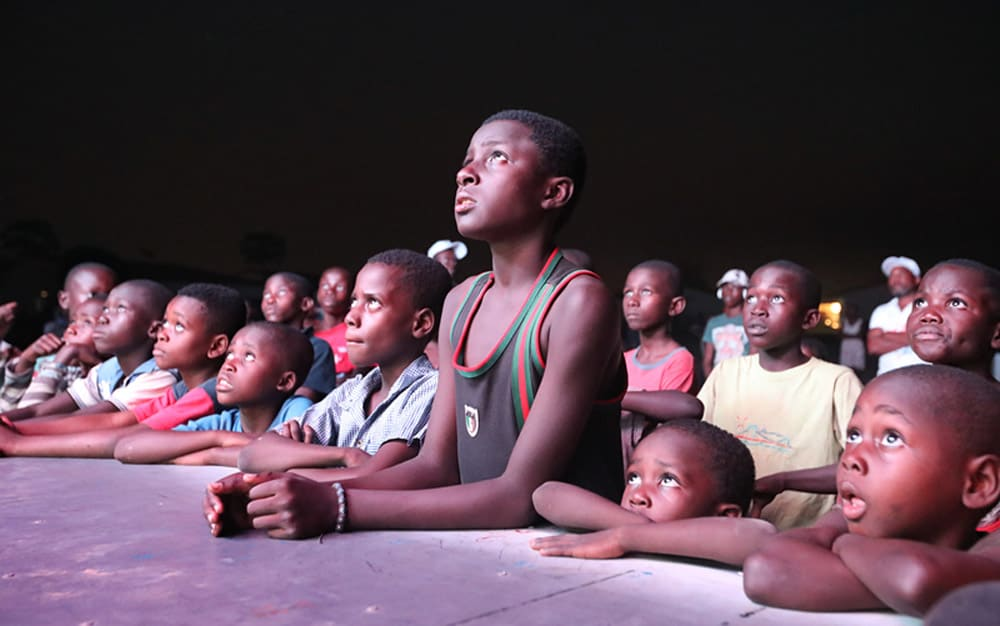 "Congolese village children engrossed in the Chinese animation ""Boonie Bears"". (photo: China Daily)"